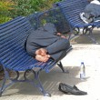 Homeless sleeping on benches - Stock Photo
