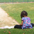Foto Stock: Young girl sitting in field