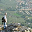 Man hiker looking over town - ストック写真