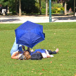 Young women with umbrella lying in a park — Stock Photo