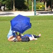 Royalty-Free Stock Photo: Young women with umbrella lying in a park