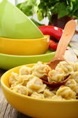 Dumplings in a bowl and wooden spoon. — Stock Photo