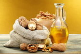 Walnut oil in bottle and nuts. — Stock Photo