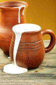 Ceramic mug with cream and clay jug. — Stock Photo