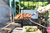 Cooking meat grilled outdoors. — Stock Photo