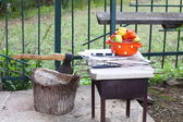 Saucepan with peppers, skewers and an ax in a wooden deck on an — Stock Photo