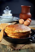Pancakes and eggs on a black background. — Stock Photo