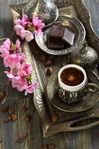 Bronze set for Turkish coffee and blossoming branch. — Stock Photo