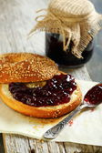 Homemade bagel with jam and tea spoon. — Stock Photo
