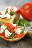 Ciabatta with tomatoes, cheese and basil. — Stock Photo