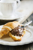 Croissant met chocolade voor het ontbijt. — Stockfoto
