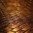 Shining golden lights on wet pavement — Stock Photo