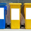 Three colorful trash cans on street - Stock Photo