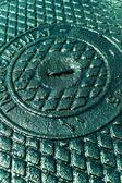 Iron sewer cover as background — Stock Photo