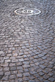 Cobble walkway with sewer cover — Stock Photo