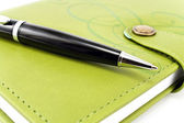 Pen and green notebook — Stock Photo