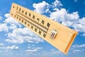 Wooden celsius fahrenheit thermometer over blue sky — Stock Photo