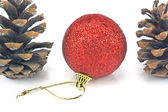 Red christmas bauble with pine cones — Stock Photo