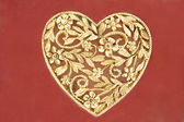 Golden heart jewelry on red background — Stock Photo