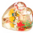 Glass heart with liquid and flowers — Stock Photo