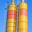 Yellow concrete silos over blue sky - Stock Photo