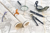 Old Maps in rolls with magnifier and compass — Stock Photo