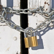 Padlock with chain on old door - Stock Photo
