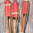 Three bamboo fire torch ion cane fence - Stok fotoğraf