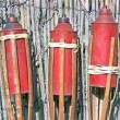 Three bamboo fire torch on cane fence - Stock Photo