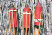 Three bamboo fire torch on cane fence — Stock Photo
