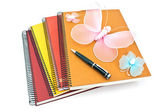 Stack of spiral notebooks with butterflies and pen — Stock Photo