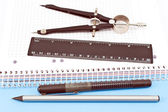 Wooden pencil, pen, drawing compass and ruler on spiral notebook — Foto Stock