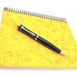 Pen on yellow spiral notebook — Stock Photo