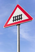 Railroad crossing sign with a barrier over blue sky — Zdjęcie stockowe