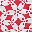 Handmade white lace on red s background — Stock Photo