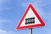 Railroad crossing sign with a barrier over blue sky — Stok fotoğraf