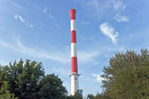 Industrial red and white chimney over blue sky — Stock Photo