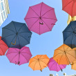 Stock Photo: Colorful umbrellas over old building and sky