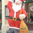 Big Santa Claus doll carrying big bag on street — Stock Photo