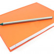Wooden pencil on red notebook isolated on white — Stock Photo #33530565