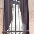Modern white wedding dress behind iron bars — Stock Photo