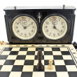 Old chess clock and chessboard on white — Stok fotoğraf