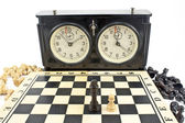 Old chess clock and chessboard on white — Stockfoto