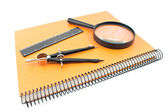 Notebook with drawing compass, ruler and magnifier isolated on w — Stock Photo