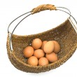 Woven basket full of eggs isolated on white — Stock Photo