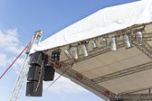 Outdoor concert stage roof construction with speakers over sky — ストック写真