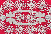 Handmade white lace on red background — Stock fotografie