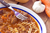 Beef goulash with pasta on wooden background — Stock Photo