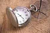 Silver pocket watch on wooden background — Stock Photo