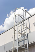 Safety metal ladder to the roof and  blue sky — Stock Photo